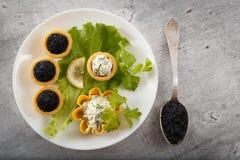 Los Tartlets llenaron de la ensalada roja y negra del caviar y del queso y del eneldo en la placa blanca contra el fondo de mader Imágenes de archivo libres de regalías