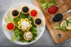 Los Tartlets llenaron de la ensalada roja y negra del caviar y del queso y del eneldo en la placa blanca contra fondo de madera r Fotografía de archivo libre de regalías