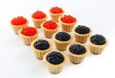 Los Tartlets llenaron del caviar rojo y negro contra fondo de madera rústico Foto de archivo