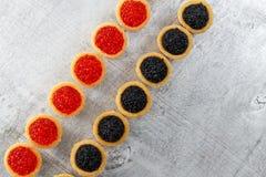 Los Tartlets llenaron del caviar rojo y negro contra fondo de madera rústico Fotografía de archivo libre de regalías