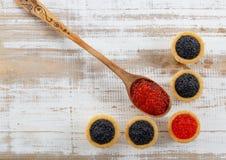 Los Tartlets llenaron del caviar rojo y negro contra fondo de madera rústico Fotos de archivo libres de regalías