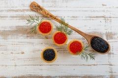 Los Tartlets llenaron del caviar rojo y negro contra fondo de madera rústico Imágenes de archivo libres de regalías
