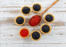 Los Tartlets llenaron del caviar rojo y negro contra fondo de madera rústico Foto de archivo libre de regalías