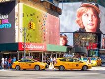 Los taxis amarillos y las carteleras coloridas ajustan a veces en New York City Imagenes de archivo