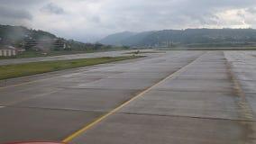 Los taxis del avión en la pista De la ventana almacen de metraje de vídeo