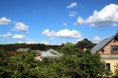 Los tejados de las casas del pueblo en el verdor de los árboles fotografía de archivo