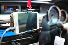 Los teléfonos elegantes se utilizan para navegar la consola dentro del coche foto de archivo libre de regalías