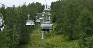 Los teleféricos que suben en austriaco alpen durante el viento del stron foto de archivo libre de regalías