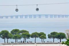 Los telef?ricos pasan por alto el puente de Vasco da Gama en el r?o Tagus fotografía de archivo