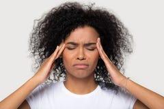 Los templos femeninos africanos jovenes del tacto del retrato del estudio sufren de dolor de cabeza fotografía de archivo libre de regalías