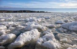 Los terrones del frazil de la nieve y del hielo en la superficie de la congelación rive imagen de archivo