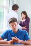 Los textos del adolescente en el teléfono como padres discuten en fondo Fotografía de archivo
