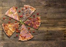 Los tipos de Diferents de pizza cortaron en la tabla de madera Foto de archivo