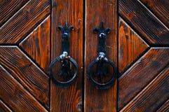 Los tiradores de puerta metálicos del vintage se ennegrecen en un fondo de madera, concepto de objetos auténticos, espacio de la  fotos de archivo libres de regalías