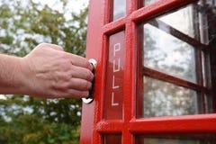 Los tirones de la mano del hombre abren la puerta roja de la caja del teléfono Fotos de archivo