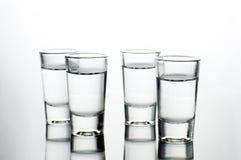 Los tiros de la vodka llenaron de alcohol en la tabla de cristal de la barra foto de archivo libre de regalías