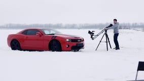 Los tiroteos comerciales, hombre joven actúan la grúa que filma el coche rojo del músculo almacen de metraje de vídeo