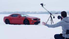 Los tiroteos, director dan instrucciones en el altavoz, coche rojo del músculo en campo de nieve almacen de metraje de vídeo