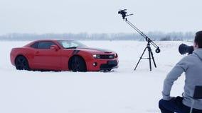 Los tiroteos, director dan instrucciones en el megáfono, coche rojo del músculo en campo de nieve metrajes