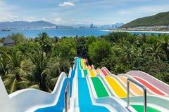 Los toboganes acuáticos de los niños en aguamarina parquean por el mar Imagenes de archivo