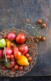 Los tomates anaranjados de los tomates de tomates de los tomates rojos coloridos del amarillo con agua caen en el fondo concreto  Foto de archivo