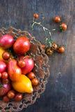 Los tomates anaranjados de los tomates de tomates de los tomates rojos coloridos del amarillo con agua caen en el fondo concreto  Fotografía de archivo libre de regalías