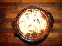 Los tomates con eneldo cocieron debajo de la corteza del queso Foto de archivo
