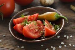 Los tomates cortados maduros, chile picante sazonan con pimienta, ajo en un tabl de madera Foto de archivo