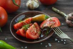 Los tomates cortados maduros, chile picante sazonan con pimienta, ajo en un tabl de madera Fotos de archivo libres de regalías
