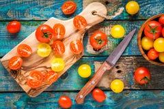 Los tomates de cereza amarillos y rojos cuted en una tabla de cortar Fotografía de archivo