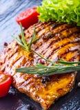 Los tomates de cereza del aceite de oliva de la pechuga de pollo del filete sazonan con pimienta y las hierbas del romero Fotografía de archivo libre de regalías