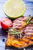 Los tomates de cereza del aceite de oliva de la pechuga de pollo del filete sazonan con pimienta y las hierbas del romero Foto de archivo