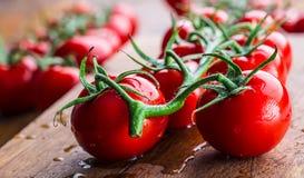 Los tomates de cereza frescos lavaron el agua potable Corte los tomates frescos Imagen de archivo