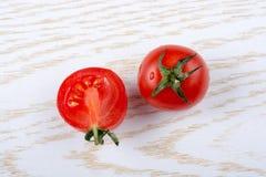 Los tomates de cereza frescos sabrosos maduros rojos cortaron por la mitad Imagen de archivo