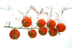Los tomates de cereza maduros rojos salpican en agua en blanco fotografía de archivo