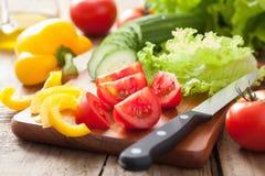 Los tomates del pepino de las verduras frescas sazonan con pimienta y la ensalada se va Imagen de archivo
