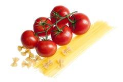 Los tomates en la vid con las gotitas de agua, agrupan los espaguetis crudos Foto de archivo