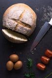 Los tomates frescos con pan hecho en casa y huevos están en la tabla de cocina Foto de archivo
