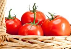 Los tomates madurados en una cesta wattled. Aún-vida en un fondo blanco Imagenes de archivo
