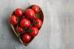 Los tomates red delicious frescos en el corazón forman la placa de madera encendido Fotos de archivo