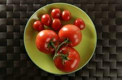 Los tomates rojos ramifican, poco los tomates grandes Imagen de archivo