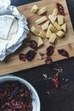 Los tomates rojos secados arreglaron con camembert italiano del queso en fondo oscuro Visión superior Comida ligera del chivato Fotografía de archivo