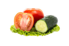 Los tomates y el pepino maduros en una ensalada hojean Foto de archivo libre de regalías