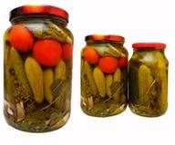 Los tomates y los pepinos conservados en vinagre en un tarro de cristal Fotografía de archivo