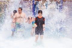 Los torists felices que gozan de la agua fría salpican en ellos en un parque del agua Imágenes de archivo libres de regalías