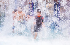 Los torists felices que gozan de la agua fría salpican en ellos en un parque del agua Imagen de archivo