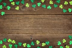 Los tréboles del día del St Patricks doblan la frontera sobre la madera rústica Fotografía de archivo