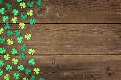 Los tréboles del día del St Patricks echan a un lado frontera sobre la madera rústica Foto de archivo