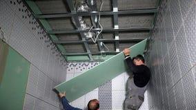 Los trabajadores aficionados instalan el tablero de la mampostería seca del yeso en techo metrajes