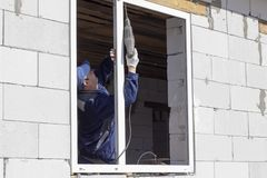 Los trabajadores asi?ticos instalan ventanas a la casa foto de archivo libre de regalías